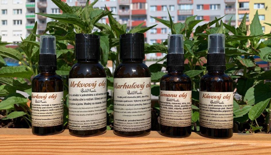 5 olejov s hnedymi etiketami stoja pred zelenymi rastlinami